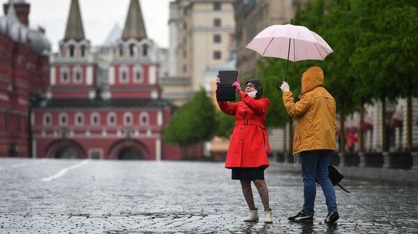 Прохожие во время дождя на Красной площади в Москве
