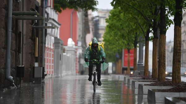 Курьер по доставке еды во время дождя на улице 1-я Тверская-Ямская в Москве