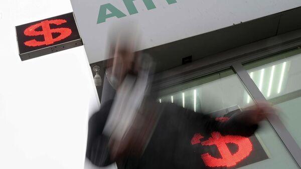 Мужчина возле электронного табло с курсом валют в Москве