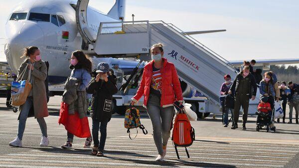 Пассажиры в защитных масках, прибывшие в Минск после карантина в аэропорту Внуково