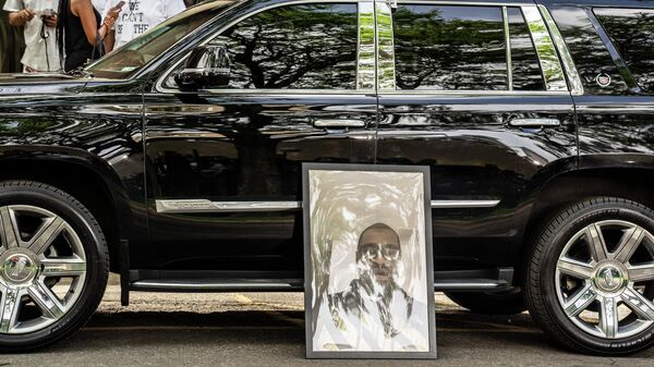Портрет Джорджа Флойда, погибшего при задержании полицией 25 мая, у машины на церемонии прощания в Северном центральном университете в Миннеаполис