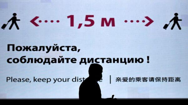Человек около информационного баннера в аэропорту Шереметьево в Москве