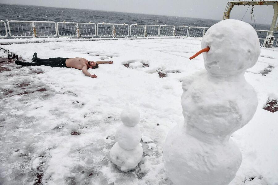 Член команды лежит в снегу на юте корабля