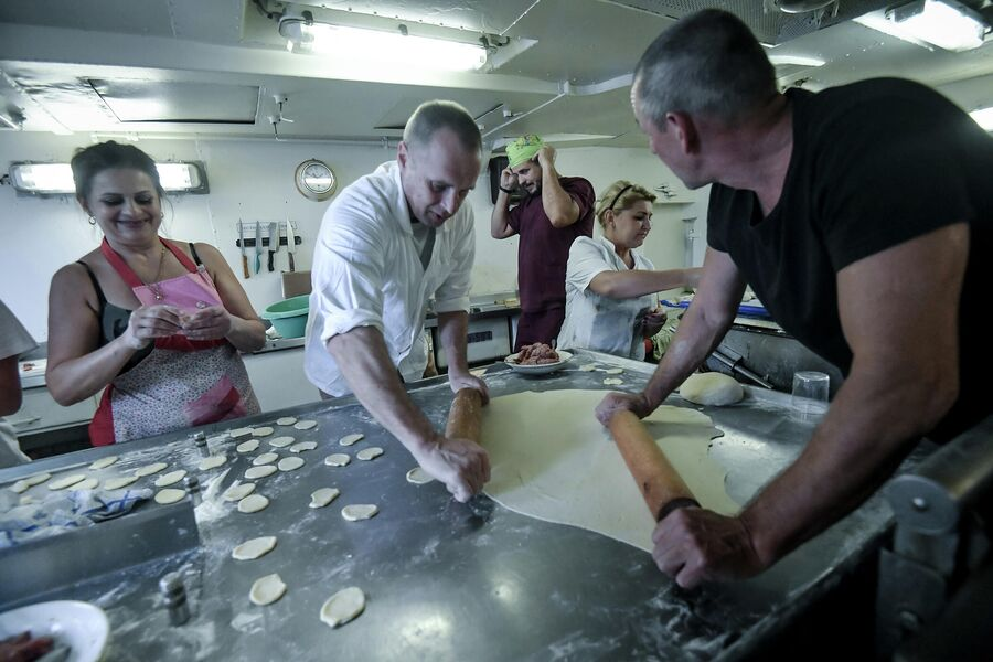Члены экипажа судна Адмирал Владимирский готовят пельмени для праздничного обеда
