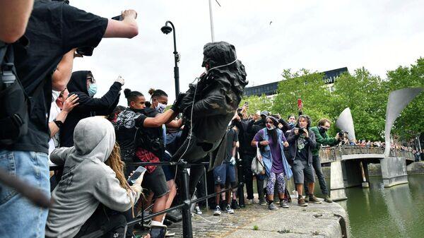 Протестующие бросают статую работорговца Эдварда Кольстона в гавань Бристоля во время акции протеста Black Lives Matter