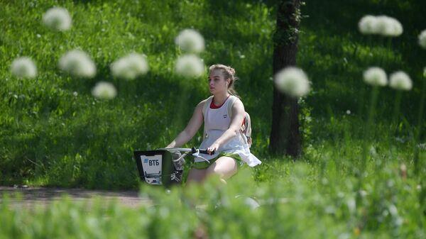 Девушка катается на велосипеде в Центральном парке культуры и отдыха имени Горького в Москве