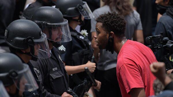 Участник акции протеста и сотрудники полиции в Голливуде