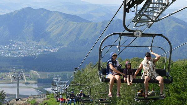 Отдыхающие в кресле подъемника на территории всесезонного курорта Манжерок в Республике Алтай