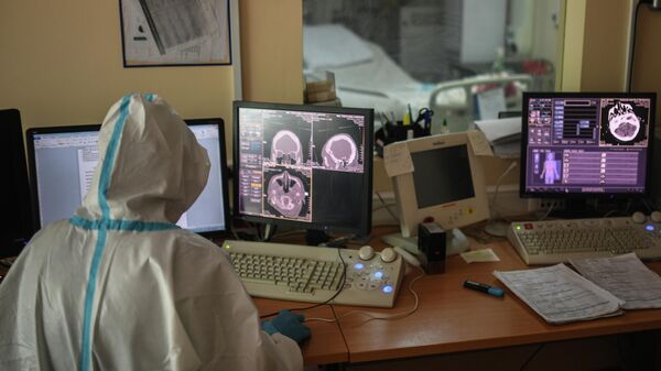 Врач городской клинической больницы № 15 имени О. М. Филатова в Москве смотрит снимки, полученные с помощью компьютерной томографии
