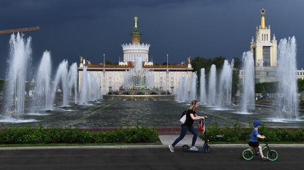 Посетители ВДНХ катаются на самокатах у фонтанов. В центре: фонтан Каменный цветок и павильон № 58