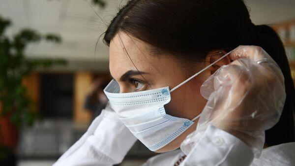 Девушка надевает маску во время демонстрации работы модельного участка для общероссийского голосования по поправкам в Конституцию РФ