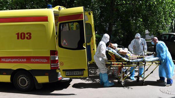 Фельдшеры и водитель скорой медицинской помощи подстанции № 34 в Москве перемещают пациента с подозрением на коронавирус  в автомобиль скорой помощи