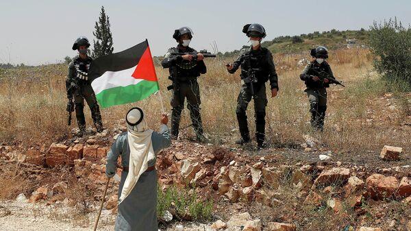 Протестующий против аннексии территорий Западного берега реки Иордан держит флаг Палестины перед израильскими военными