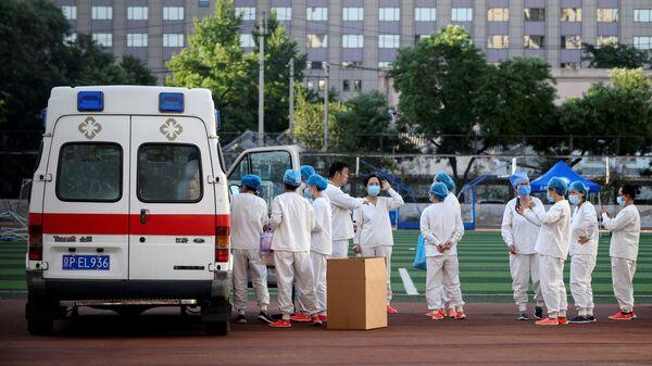 Медицинские работники в спортивном центре Guang'an, где проходит тестирование людей на коронавирус, живущих рядом или посещающих рынок Синьфади