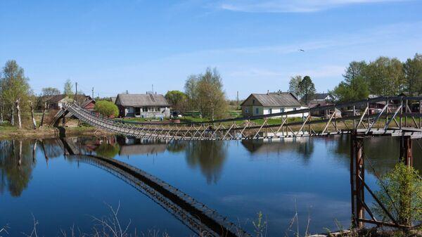 Подвесной деревянный мост через реку Олонку в деревне Татчелица