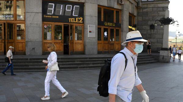 Температура 31 градус на табло на Тверской улице в Москве