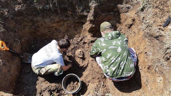 Участники поискового движения во время раскопок захоронения мирных жителей близ деревни Моглино Псковской области