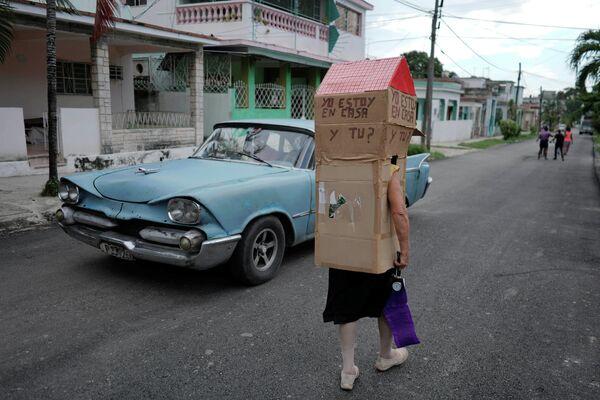 Пенсионерка и бывшая медсестра Феридия Рохас идет по улице Гаваны во время пандемии коронавируса, надев картонную коробку с надписью Я дома. А ты?