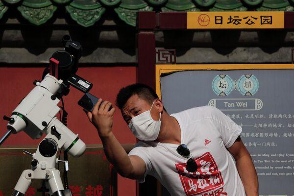 Мужчина снимает  солнечное затмение в Пекине, КНР