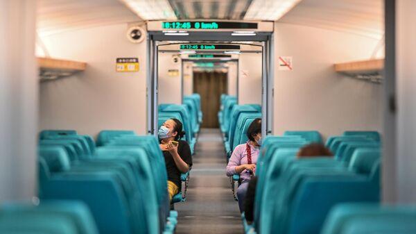 Пассажиры в защитных масках в вагоне поезда Шанхайского маглева