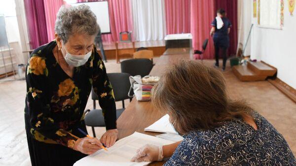 Член избирательной комиссии регистрирует участницу голосования по внесению поправок в Конституцию РФ на избирательном участке №209 в Чите