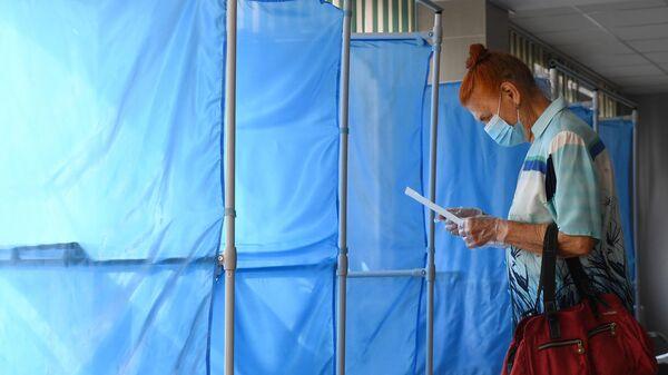Женщина принимает участие в голосовании по внесению поправок в Конституцию РФ на избирательном участке №1503 в Новосибирске