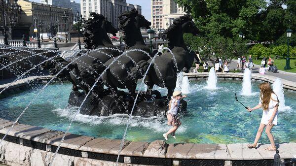 Дети играют возле фонтана в жаркий день на Манежной площади в Москве