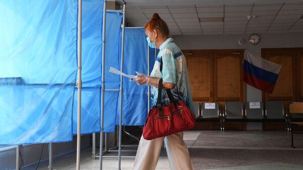 Женщина принимает участие в голосовании по внесению поправок в Конституцию РФ на избирательном участке
