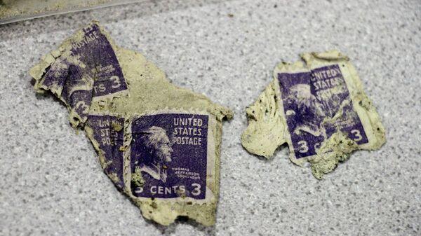Марки в три цента, найденные при раскопках самолета, который врезался в гору в 1952 году в штате Аляска