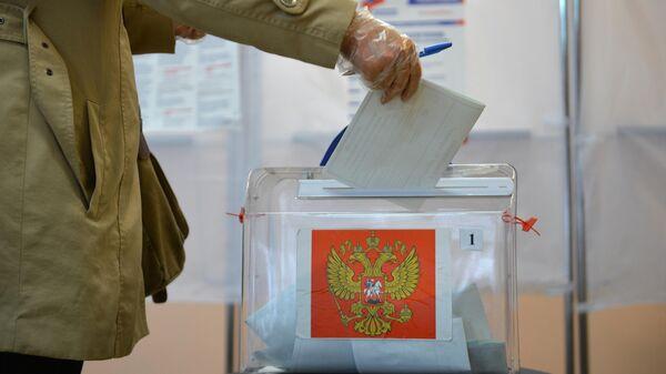 Женщина принимает участие в голосовании по внесению поправок в Конституцию РФ