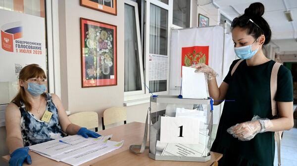Девушка принимает участие в голосовании по внесению поправок в Конституцию РФ на одном из избирательных участков в Сочи