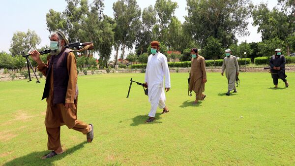 Члены Талибана во время передачи оружия