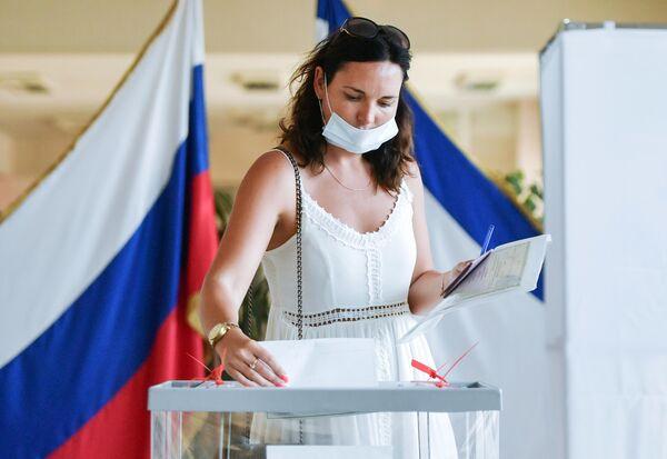 Женщина принимает участие в голосовании по внесению поправок в Конституцию РФ на одном из избирательных участков в Симферополе