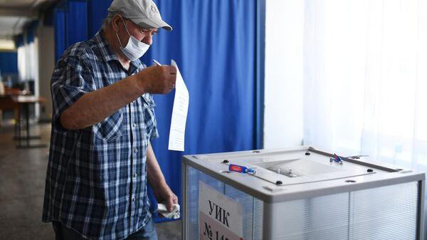 Мужчина голосует по вопросу внесения поправок в Конституцию РФ на избирательном участке в Новосибирске