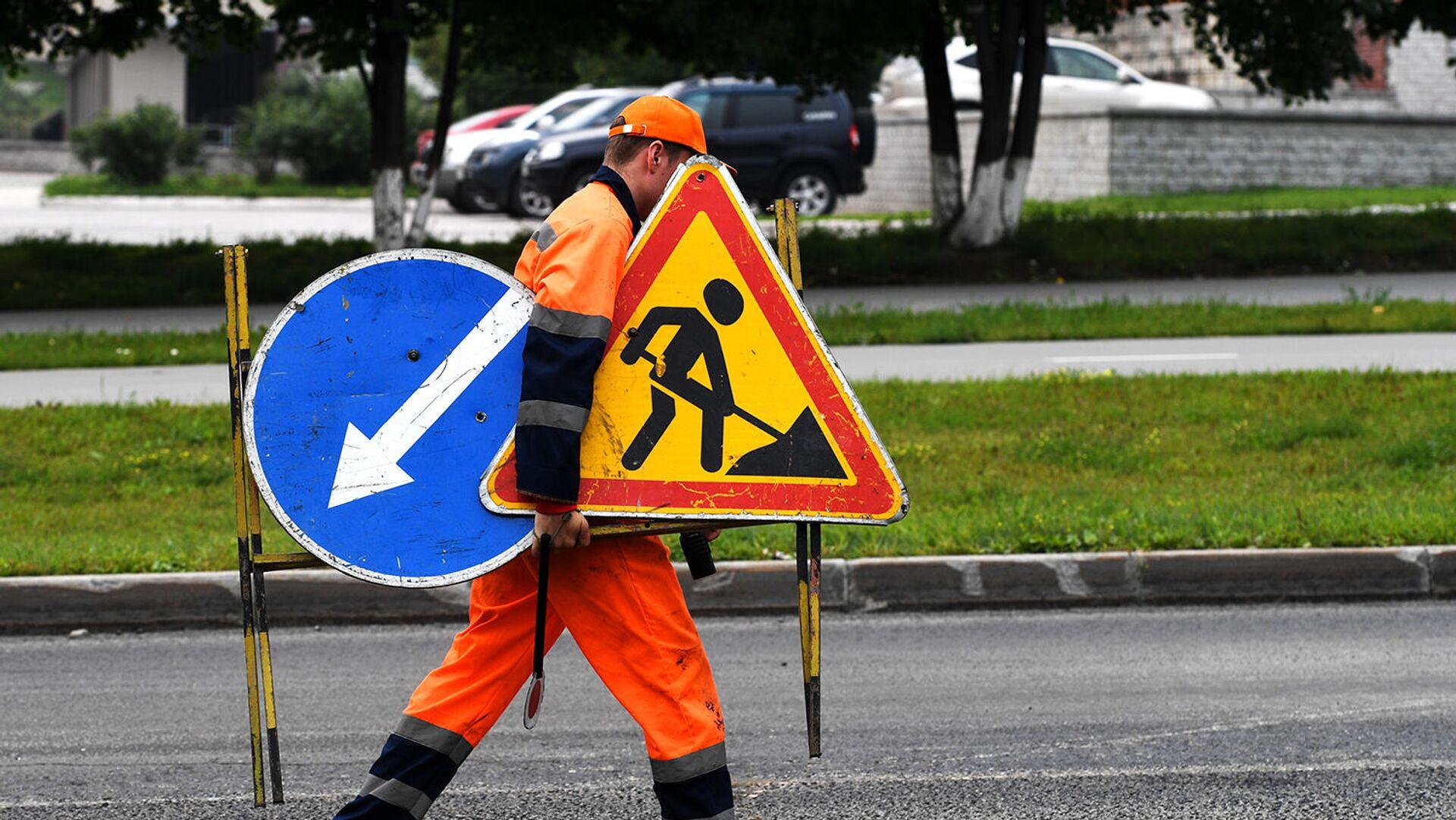 Рабочий переносит дорожные знаки во время укладки верхнего слоя дорожного покрытия - РИА Новости, 1920, 18.05.2021