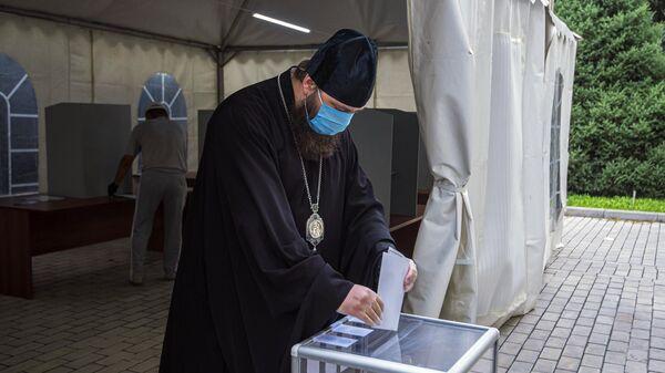 Священнослужитель принимает участие в голосовании по внесению поправок в Конституцию РФ на избирательном участке в Бишкеке