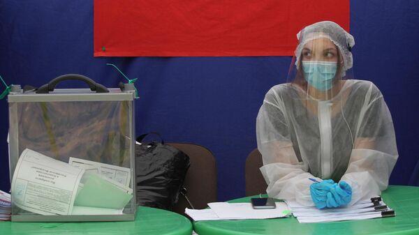 Волонтер в защитной маске на избирательном участке в Барнауле