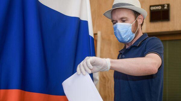 Мужчина голосует по вопросу изменений в Конституцию России на избирательном участке
