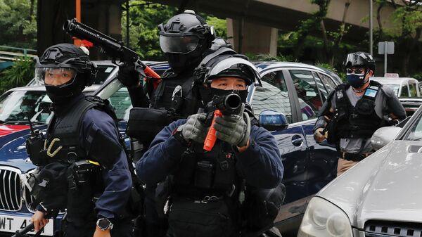 Сотрудники спецслужб во время протеста против закона о национальной безопасности Гонконга