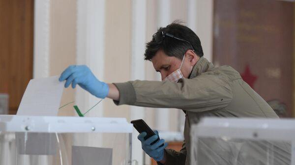 Мужчина фотографирует бюллетень во время голосования по вопросу одобрения изменений в Конституцию РФ