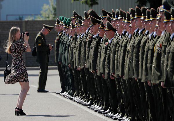 Женщина фотографирует выпускников Военной академии Беларуси в Минске
