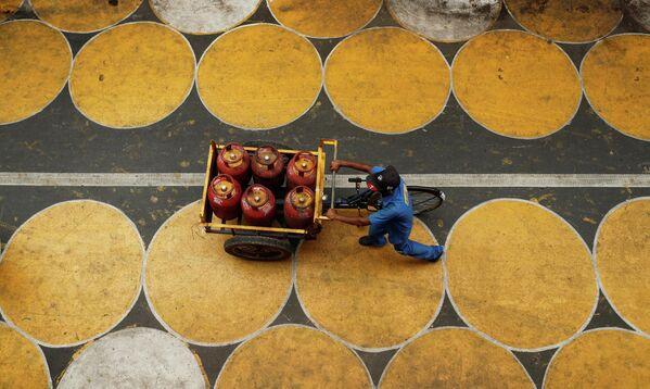 Мужчина толкает тележку с баллонами со сжиженным нефтяным газом в Мумбаи, Индия