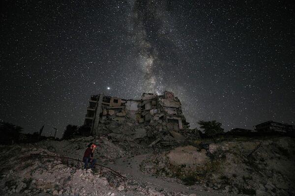 Мужчина у разрушенного здания в сирийском городе Эриха