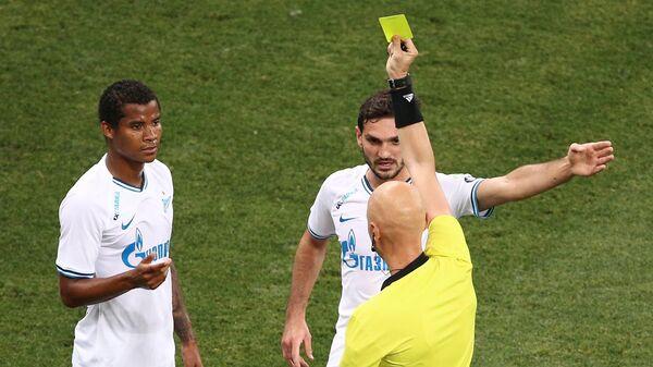 Сергей Карасев показывает желтую карточку игроку Зенита Вильмару Барриосу (слева)