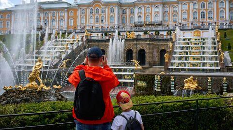 Посетители фотографируют фонтаны Большого каскада в Нижнем парке Государственного музея-заповедника Петергоф