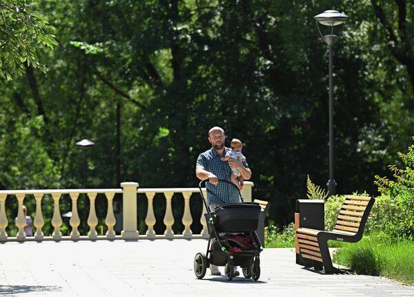 Мужчина гуляет с ребенком в парке Сад будущего в Москве