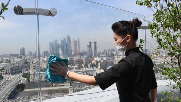 Сотрудница в защитной маске на летней веранде ресторана Сахалин в Москве