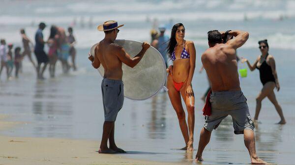 Девушка позирует фотографу на пляже в Сан-Диего, Калифорния