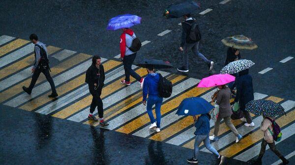 Прохожие переходят через дорогу во время грозы на одной из улиц в Москве