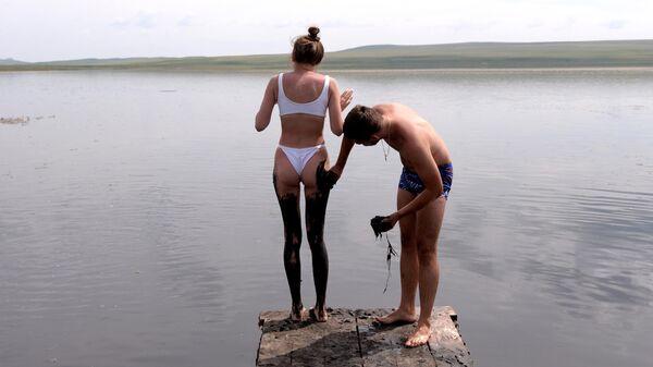 Мужчина намазывает девушку высокоминерализованной сульфидной грязью из донных отложений горько-соленого озера Тус в Ширинском районе Республики Хакасия